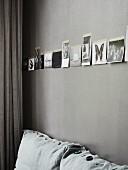 Schwarz-weisse Fotos an grau getönter Wand über Sofapolster mit verschiedenen Schmuckknöpfen