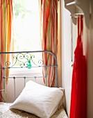 Romantisches Metallbett mit Kissen vor dem Fenster