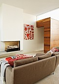 Back of sofa with view of fireplace and wooden wall element; red and white painting and scatter cushions
