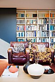 Scuffed, vintage leather armchairs in front of bookcase; vase of twigs in foreground