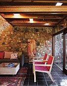 Wooden armchairs with pink fabric woven seats and backs, sofa and box table in front of stone wall; sliding glass wall leading to garden and wooden deck ceiling with lighting elements