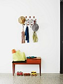 Sparsely furnished hallway with shoes below bench and hats and summer tops on classic coat rack (Hang it all)