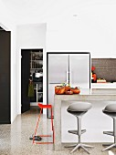 Detail of modern kitchen with side-by-side fridge freezer and stools at concrete breakfast bar; view into pantry through open door to one side