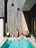 Children next to pool of Australian beach house against wooden facade weathered to a silvery grey