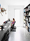 Narrow home office with black furniture and flotsam artwork above long desktop opposite bookcase