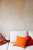 Kissen mit farbigem Samtbezug auf heller Couch vor Wand mit Sandsteinfliesen
