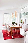 Wooden table and chairs with white upholstery on red, patterned rug in modern dining room