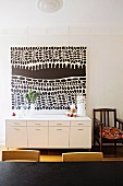 Modern black and white painting above white sideboard next to simple, wooden armchair with cushion