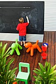 Toys on wooden floor of terrace; little boy drawing on large blackboard