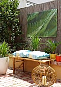 Wicker lantern on terracotta floor in front of bamboo bench with cushions and photo print on screen fence in courtyard