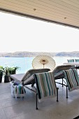 Sun loungers and small parasol on roofed terrace with glass balustrade and sea view