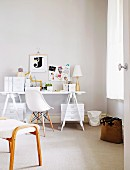 View through open door into white home office - desktop on wooden trestles, stacked storage boxes and classic chair