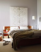 Painting of stylised tree above wooden headboard of double bed against grey-painted wall; designer standard lamp in corner
