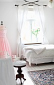 Boudoir - old piano stool at dressing table and single bed with lacy throw below window
