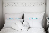 Double bed with heart-shaped scatter cushions and stacked pillows in rustic atmosphere