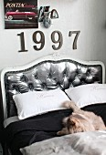 Double bed with curved headboard upholstered in silver; ornamental numbers and retro lamp on wall