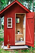 View in through open door of Swedish outdoor toilet in wooden hut painted falu red