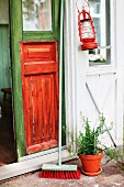 Hurricane lamp and broom outside front door painted in bright green and orange