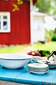 Stack of plates and enamel bowl on blue-painted garden table with Swedish, Falu red wooden house in background