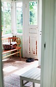 View of bench and chair in porch of old, Swedish wooden house