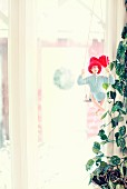 Doll wearing red bobble hat on swing next to houseplant in front of window