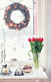 Wreath with fairy lights hung in window, gnome figurine and vase of red tulips on white vintage tray