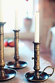 Lit candles in nostalgic, patinated brass candlesticks