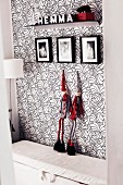 Black, white and red; floral wallpaper, gnome figurines, family photos and decorated bracket