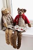 Winterlich verkleidete Teddybären auf einem Fensterbrett