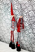 Figurines wearing gnomes' hats leaning against wall with floral wallpaper