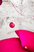 Cushions, Christmas bauble and string of beads in bright magenta on and around white, artificial Christmas tree