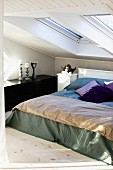 Double bed with blanket and scatter cushions below skylights in vintage attic bedroom