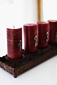 Dark red Advent candles in rusty, rectangular candelabra