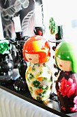 Japanese Kokeshi dolls in bright colours and black candlesticks on sunny windowsill