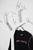 Black cardigan hanging on coat rack in shape of stylised tree made from white-painted wood
