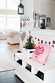 Pink cushion next to small, decorated Christmas tree in crate on white cloakroom bench in front of armchair in open-plan interior