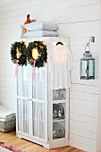 Christmas wreaths of fir branches and ribbons hanging on cupboard door in rustic interior with white wood cladding