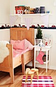 Kinderstuhl als Tierfigur auf Boden vor weißem Nachttisch und Kinderbett aus Holz in ländlichem Kinderzimmer