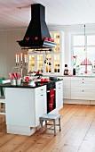 Schwarzer Dunstabzug über Küchenblock mit weißem Unterschrank auf Dielenboden in skandinavischer Landhausküche