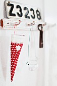 Festive bag for sweets made from red, polka-dot fabric hanging from shabby-chic wall hooks below number plate