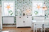 Dining room with floral wallpaper, white-painted, country-house-style furniture and festive star ornaments in windows