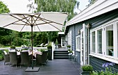 Modern outdoor furniture and white parasol on terrace; terrace floor and house facade in dark wood panelling