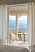 Blick vom Schlafzimmer durch offene Tür auf Balkon mit Tisch und hellen, modernen Stühlen