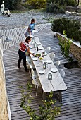 Blick von oben auf lange Tafel aus verwittertem Holz und weiss Stühle, auf Holz Terrassenboden vor mediterranem Garten, Frauen beim Tisch decken