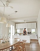Dining area with classic wooden chairs, adjustable pendant lamps with white lampshades; woman in open-plan, modern kitchen in background