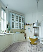 Shell chair with metal frame at white table below retro pendant lamp in country-house kitchen