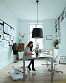 Woman at table below pendant lamp with black lampshade in study with fitted bookcase
