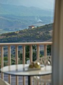 Blick durch Fenster über Balkon auf Berglandschaft und mediterranes, freistehendes Wohnhaus