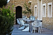 White outdoor chairs around rustic wooden table on terrace adjoining Mediterranean stone house
