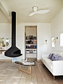 Suspended, cast iron fireplace, classic coffee table and white sofa in simple living room